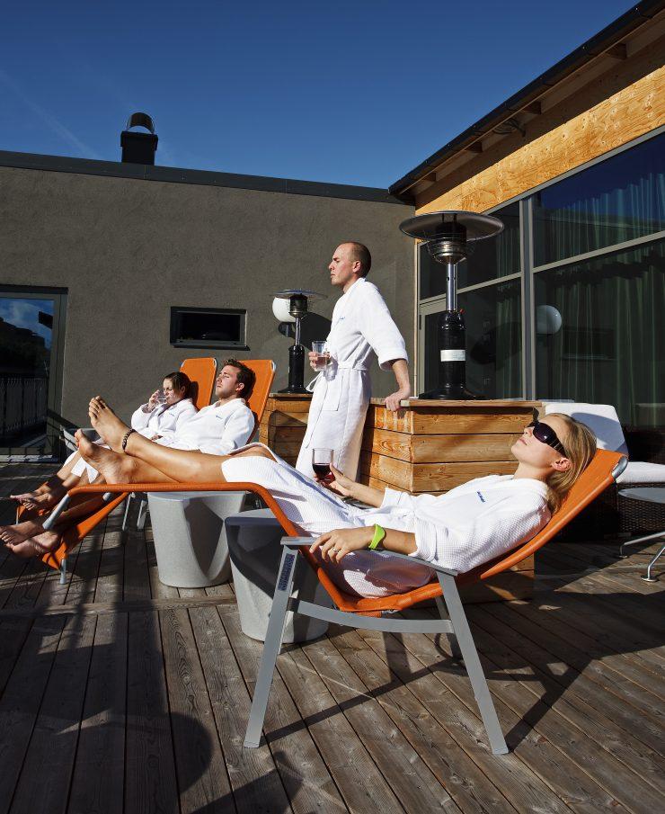 Personer njuter i solen på terrassen