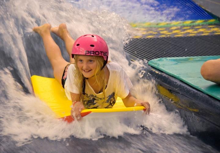 Flicka surfar bodyboard